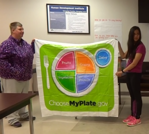 Brandy and Monica co-facilitators of the Health Partners program hold up the MyPlate mat for a food matching game