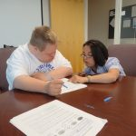 megan mccormick with student doing paperwork