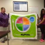holding up choosemyplate.gov banner